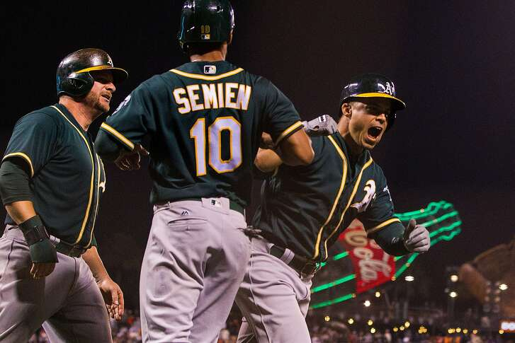 SAN FRANCISCO, CA - JUNE 28: Jake Smolinski #5 of the Oakland Athletics celebrates with Marcus Semien #10 and Stephen Vogt #21 after hitting a three run home run against the San Francisco Giants during the eighth inning at AT&T Park on June 28, 2016 in San Francisco, California. The Oakland Athletics defeated the San Francisco Giants 13-11.  (Photo by Jason O. Watson/Getty Images)