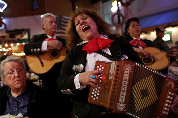 Eva Ybarra (center) sings with Ricardo Urbano and Maria Ruiz at Chris Madrid's as Nora Catlett, 88, left, dines with her family in San Antonio on Friday, Dec. 18, 2015.