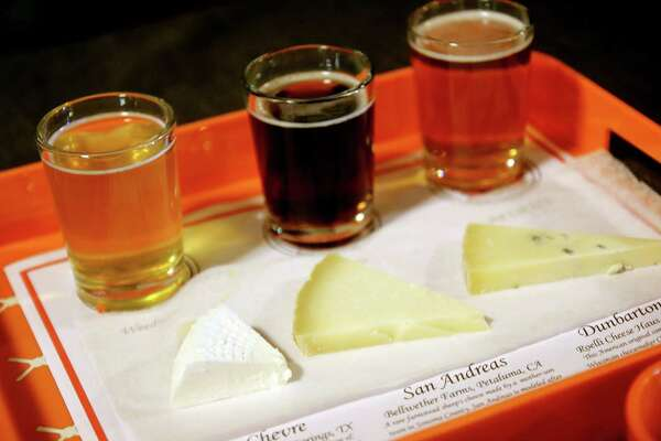 Jordan Smith, left, and Nicole Buergers of  the Houston Dairymaids serve flights of cheese and beer at Saint Arnold Brewing Company. The recurring cheese-and-beer pairing is held every fourth Friday at Pub Night at the brewery, 2000 Lyons Avenue.  The Dairymaids store is located at 2201 Airline Drive.