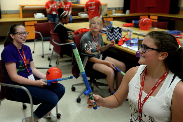 Mia Pierce, left, and Aidan Watson, center, watch as Haleigh Vincent levitates a piece of foil with a static electricity generator at Lamar University's x-plore LUEE camp for middle school girls on Monday afternoon. The camp aims to stir interest in electrical engineering among girls.  Photo taken Monday 6/27/16 Ryan Pelham/The Enterprise