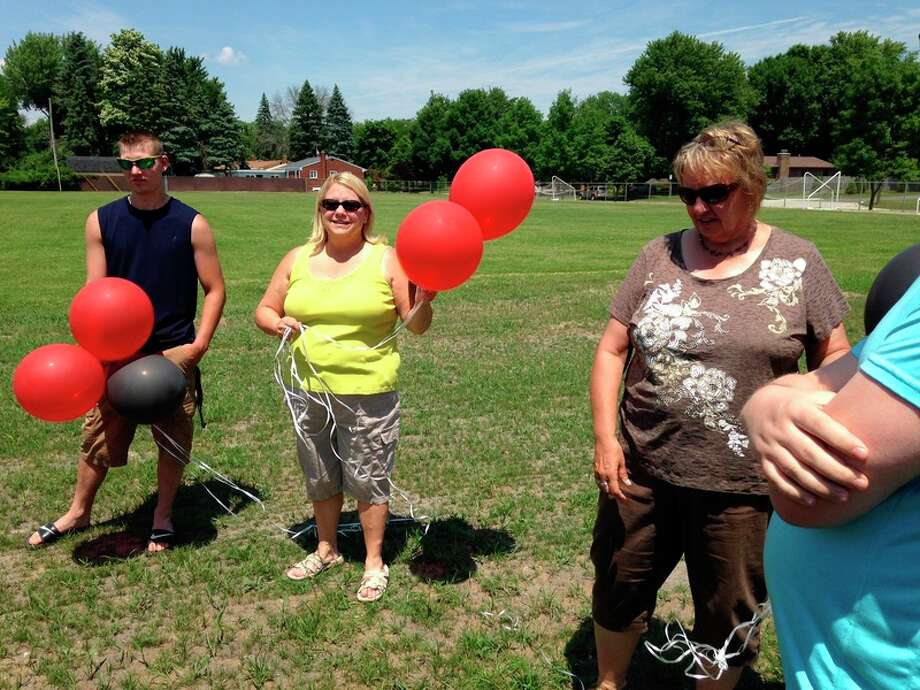 Photo courtesy of Ali Geer From left, Justin Monville, Anne Hinson and Julie Gamm take part in the remembrance of Parkdale Elementary School and Seth Enszer, a classmate who died recently.