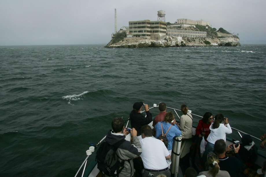 """Tourists to San Francisco ride under the Golden Gate Bridge and and around the Alcatraz Island on Captain Frank's fishing the """"Lovely Martha."""" Photo: Mike Kepka, The Chronicle"""