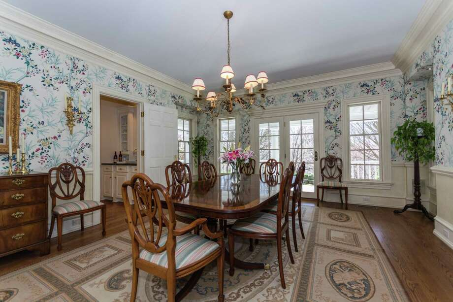 The formal dining room, also with French doors leading to the covered porch, features heavily detailed crown molding, classic chair rail and an attached butler's pantry with a wet bar and glass cabinetry.