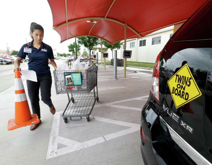 3. Nicole Cappelli, an H-E-B store manager, delivers a cart full of groceries to Leal, a 32-year-old mother of young twin daughters. Leal estimates the curbside-pickup service saves her 1½ hours per grocery trip. At least 10 other stores and third-party businesses offer delivery or pickup services in the Houston area.