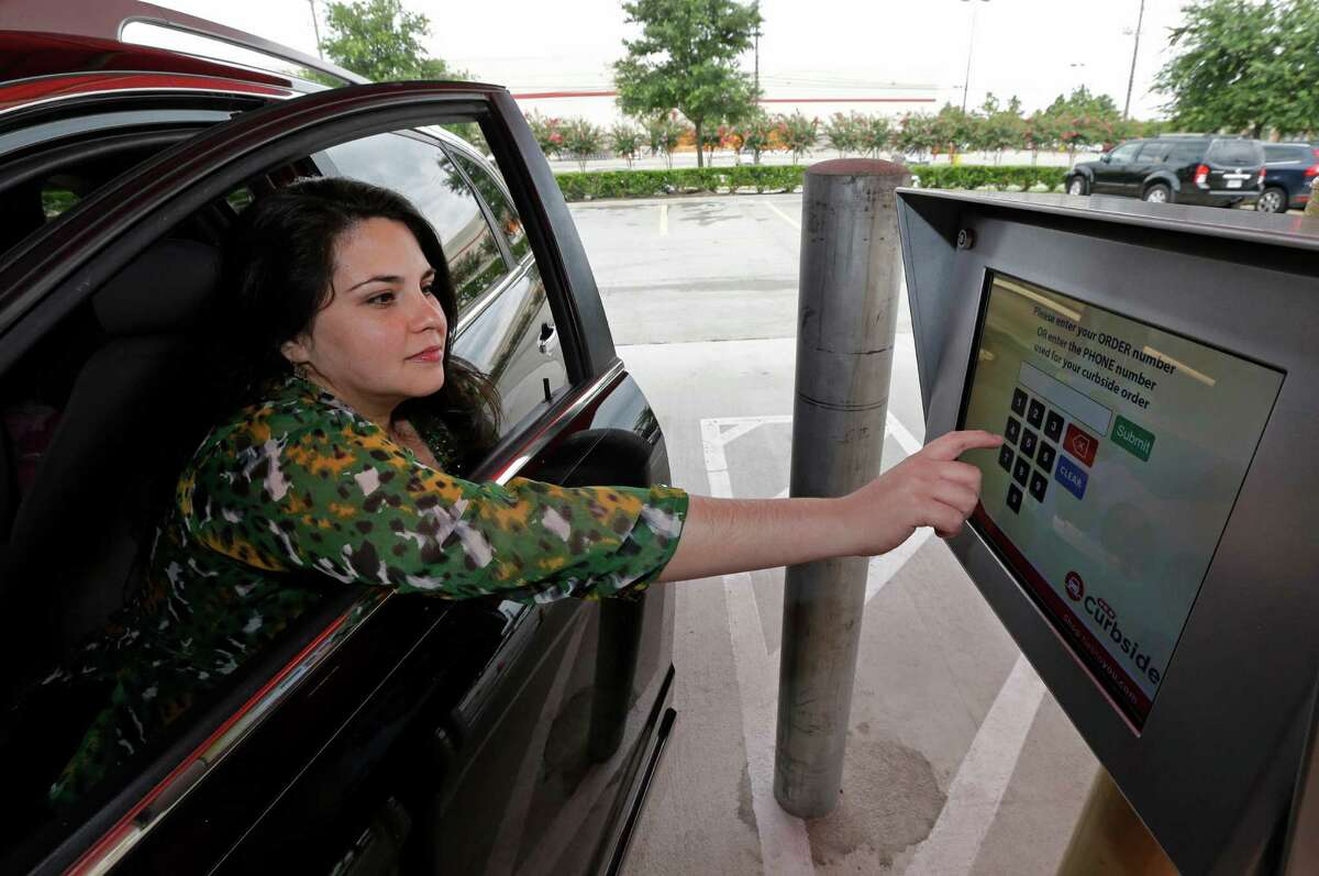 2. Monica Leal drives from her home in Cypress to the H-E-B on Bunker Hill to pick up her order. She can pay the bill and the $4.99 convenience fee without having to step out of her car.