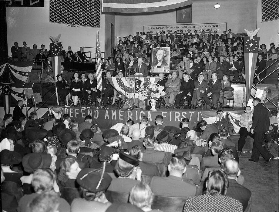 Famed aviator Charles Lindbergh stands at the podium in front of a large portrait of George Washington to address an audience attending a rally of the America First Committee in Fort Wayne, Ind., in 1941. Photo: Associated Press