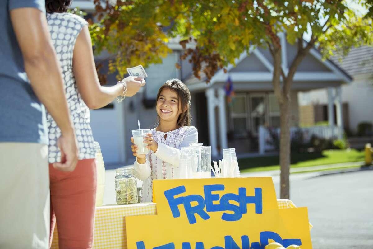 Girl selling lemonade at lemonade stand