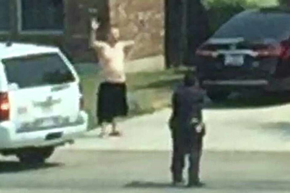 A video frame grab shows Gilbert Flores with his hands in the air and two Bexar County deputies, guns drawn, attempting to arrest Flores. Less than a second later, Flores would be shot and killed by the deputies. The video was shot by a neighbor and was released by the sheriff's department on Friday, 12/11/15.