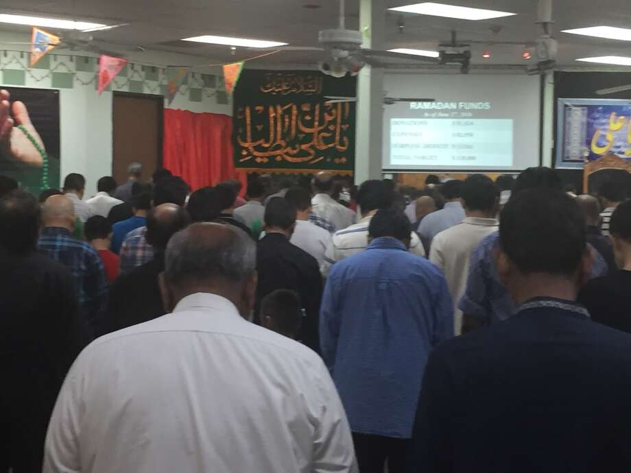 Men bow their heads in prayer at the Islamic Education Center of Houston, during a local celebration of the Night of Power, the 23rd night of the month of Ramadan.