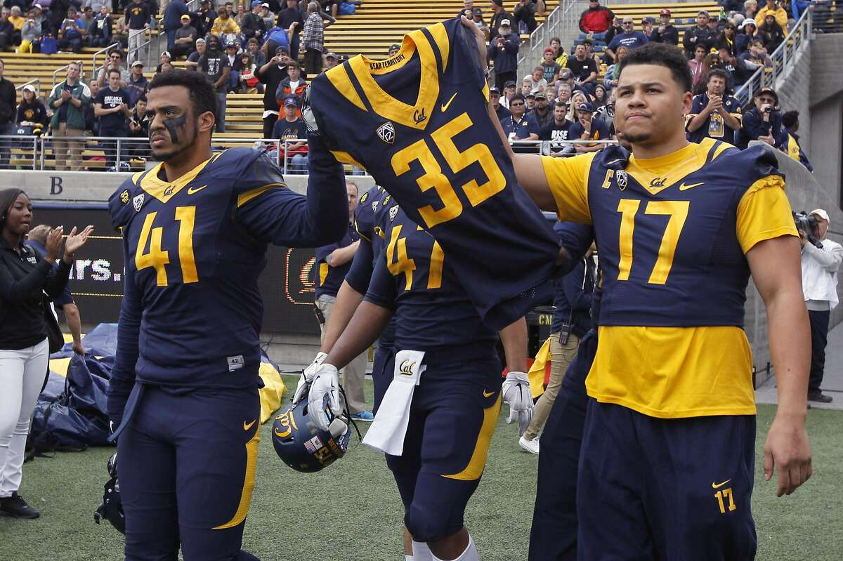 Cal Bears players carry the jersey of Ted Agu, to honor the teammate who died after a preseason training session, before the game against the BYU Cougars at Memorial Stadium in Berkeley, Calif. on Saturday, Nov. 29, 2014.