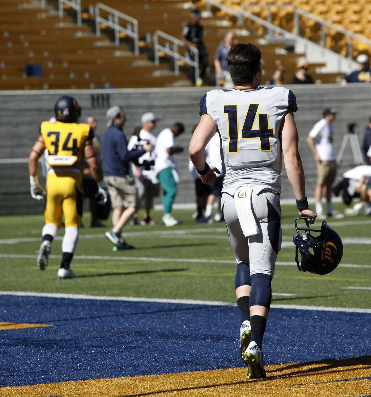 Quarterback Chase Forrest along with Fabiano Hale, #34, run on to the field with their helmets before UC Berkeley's Cal Football Spring Scrimmage in Berkeley on April 16, 2016