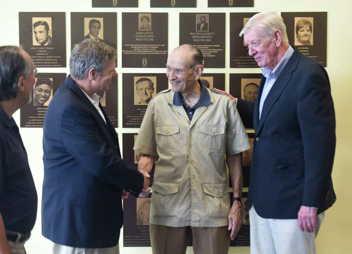 New Canaan football coach Lou Marinelli, left, Darien equestrian Bill Steinkraus, center, and Stamford (Trinity Catholic) basketball and Babe Ruth League baseball coach Mike Walsh congratulate each other after being inducted during the Fairfield County Sports Commission Hall of Fame induction ceremony at the UConn Stamford campus in Stamford, Conn. Wednesday, June 29, 2016. The 2016 inductees are Fairfield PGA pro J.J. Henry and Norwalk WNBA pro Rita Williams into the Jackie Robinson Professional Wing; Bridgeport basketball player Manute Bol, New Canaan basketball player Maurice Gilmore and Darien equestrian Bill Steinkraus into the James O'Rourke Amateur Wing; and New Canaan football coach Lou Marinelli and Stamford (Trinity Catholic) basketball and Babe Ruth League baseball coach Mike Walsh.