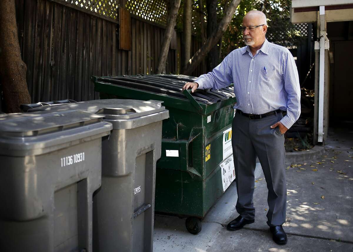 Co-plaintiff Stephen Clayton looks down at the garbage cans at a rental property he owns in Oakland, California, on Wednesday, June 29, 2016.