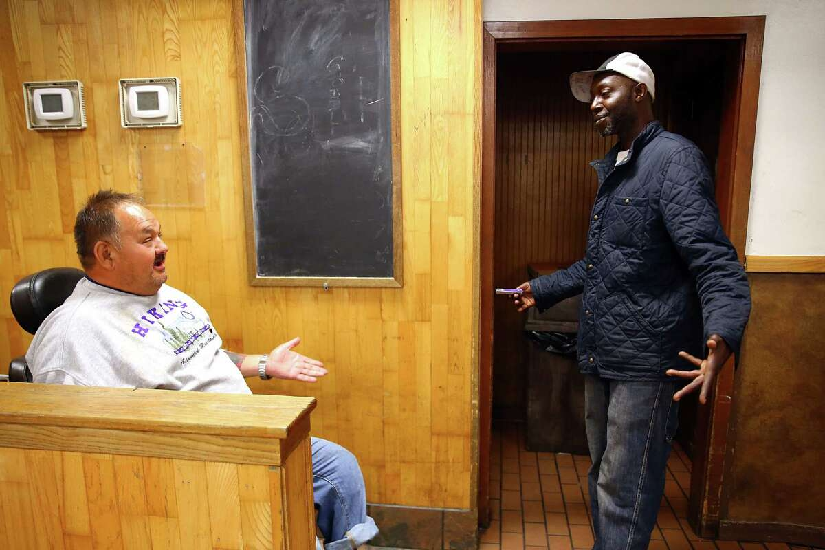 Charlie and Marcus, both regulars at the Union Gospel Mission, talk in the day room after breakfast, Wednesday, June 29, 2016.