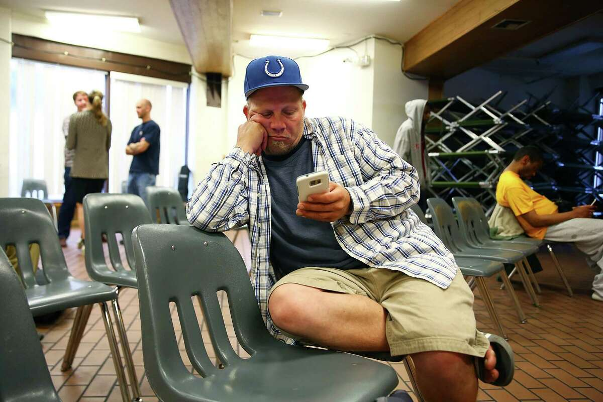 Mike checks his phone in the day room of Union Gospel Mission in downtown Seattle, June 29, 2016. At night the day room and cafeteria are lined with cots for guests to sleep on.