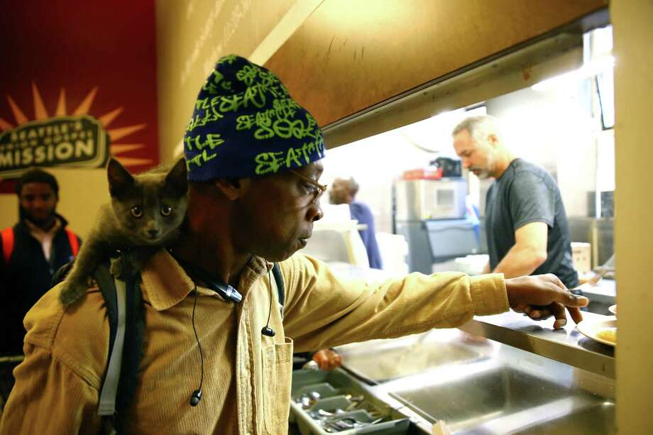 With is 11-week old kitten Lucy on his shoulder, Melvin Harris gets a plate of breakfast at the Union Gospel Mission, June 29, 2016.  Harris has been coming to UGM on and off for the past six months. Photo: GENNA MARTIN, SEATTLEPI.COM / SEATTLEPI.COM