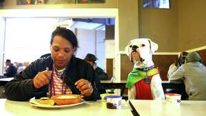 Donna Nelson, sits with Lucky, as she eats breakfast at the Union Gospel Mission, June 29, 2016.  Though UGM's downtown location is a men's only shelter at night, women are allowed to eat meals and stay there during daytime hours.