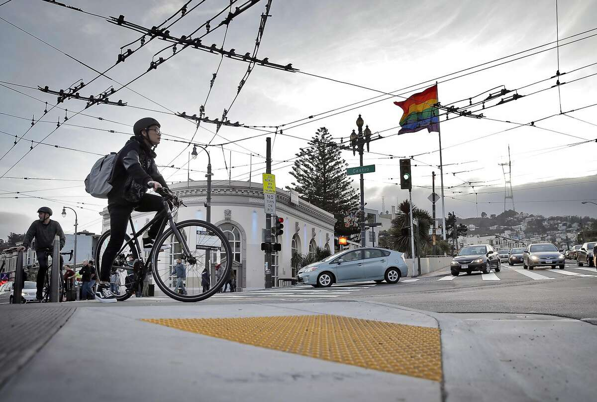 Bicyclists waits to cross Market Street on a bulb-out at the intersection of Market and Castro Streets in San Francisco, Calif., on Sunday, January 11, 2015. Emergency responders have voiced opposition to the bulbouts saying they interfere with their response times, but pedestrian advocates say they make it safer for pedestrians to cross busy streets.
