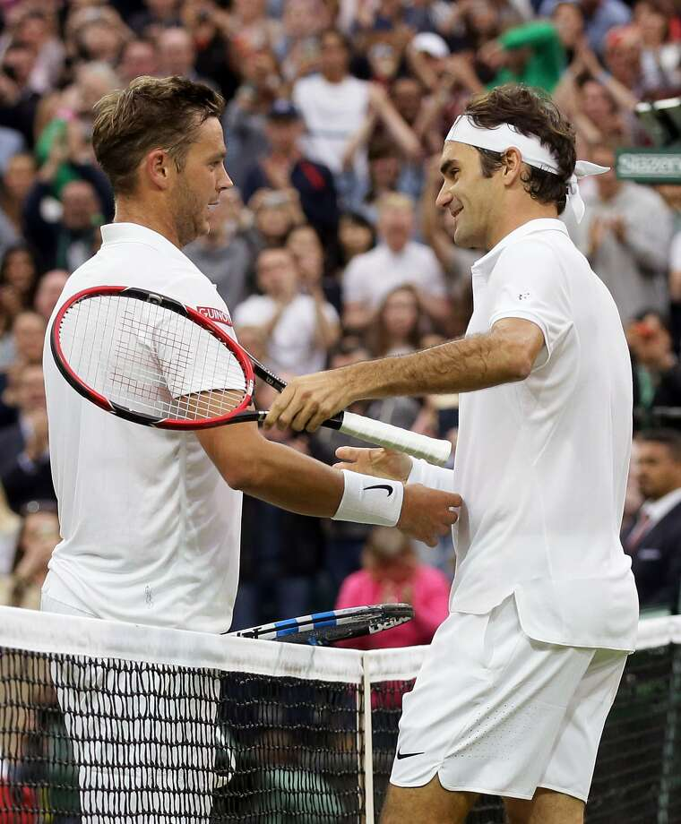 Roger Federer (right) congratulates Marcus Willis after Federer prevailed. Photo: Tim Ireland, Associated Press