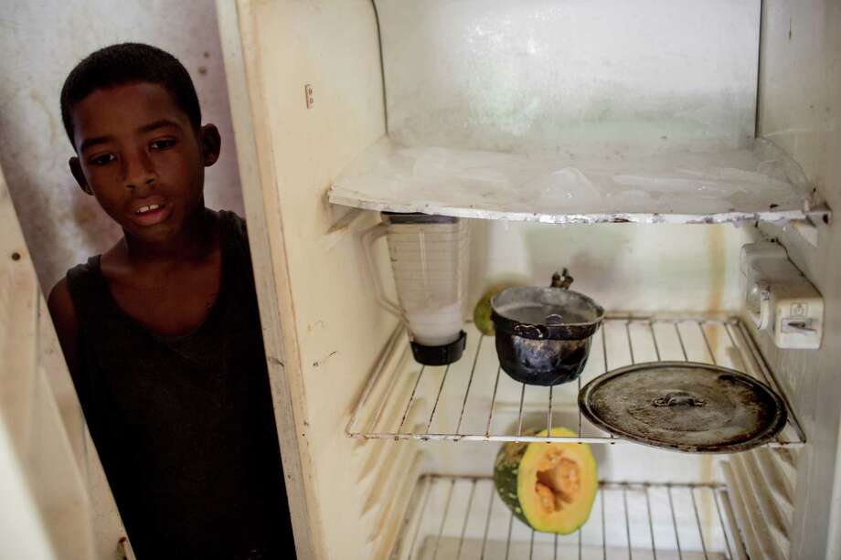 Joffren Polanco stands beside his almost empty fridge in Caracas. MUST CREDIT: Alejandro Cegarra for The Washington Post. Photo: THE WASHINGTON POST, For The Washington Post / THE WASHINGTON POST