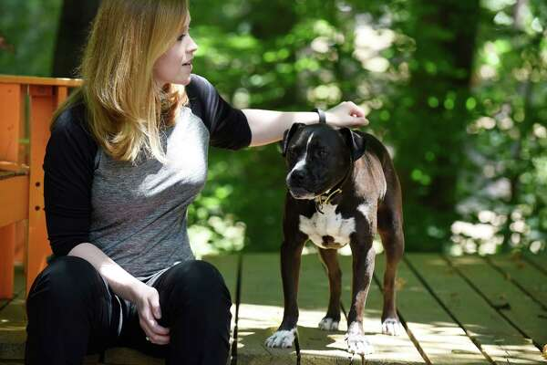 Bronwen Dickey, pictured with her friend's pit bull mix, has received strong support and bitter criticism over her new book about pit bulls. MUST CREDIT: Photo by Liz Condo for The Washington Post.