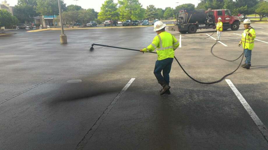 Workers in Austin apply an asphalt emulsion seal-coating product to a parking lot. This product would still be allowed under a proposed San Antonio ordinance that would ban sealants made from coal tar. Photo: Courtesy Of Tom Ennis