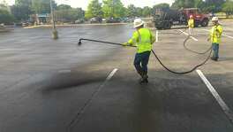 Workers in Austin apply an asphalt emulsion seal-coating product to a parking lot. This product would still be allowed under a proposed San Antonio ordinance that would ban sealants made from coal tar.