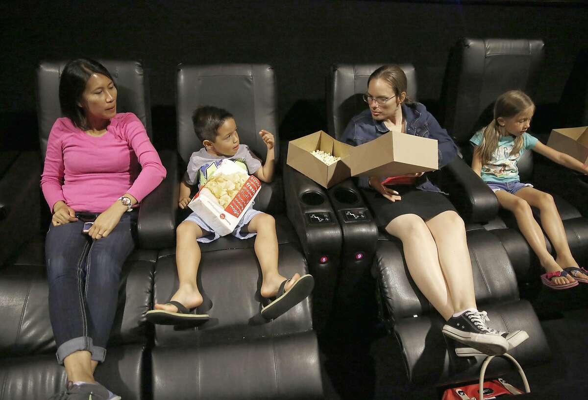 Left to right--Maryann Martin, Cameron Martin, 5 years old, Stephanie (prefers no last name), and Chloe Martin, 6 years old, check out the chairs and get ready to experience their first Dolby cinema movie at AMC in Newpark Mall on Wednesday, June 29, 2016, in Newark, Calif. Reserved recliners in foreground not only recline but pulsate according to story line.