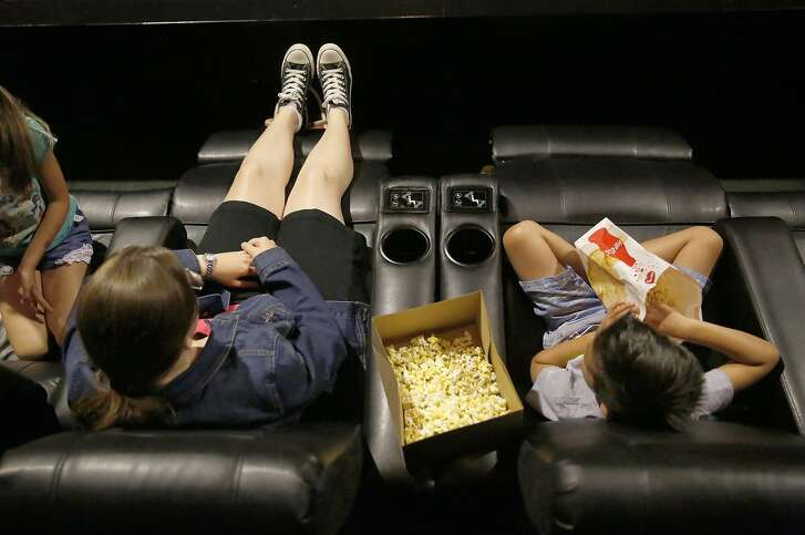 Movie goers sit on recliners in one of the theaters at AMC in Newpark Mall on Wednesday, June 29, 2016, in Newark, Calif.   Reserved recliners not only recline but pulsate according to movie action.