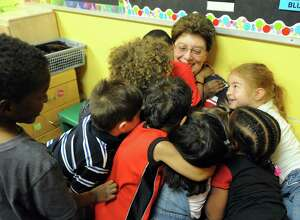 Christine Knapp, gets a hug goodbye from some of her current students, is retiring after 45 years as a teacher at the Schenectady Day Nursery on Friday June 24, 2016 in Schenectady, N.Y. (Michael P. Farrell/Times Union)