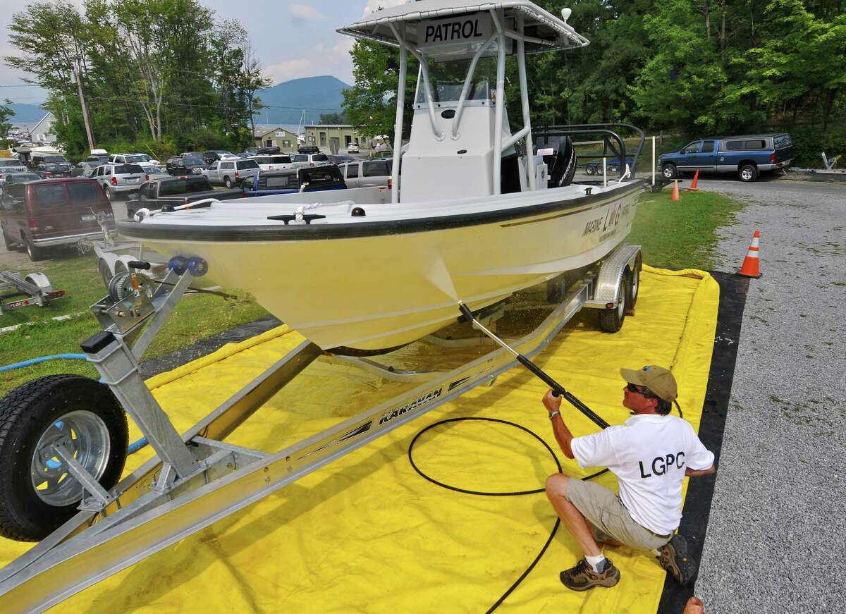 Doug Underhill of The Lake George Park Commission demonstrates how to pressure wash a boat to keep invasive species from being brought into the lake by boaters on Aug. 9, 2012 in Bolton Landing, NY. Keep clicking for more information about the states invasive species.