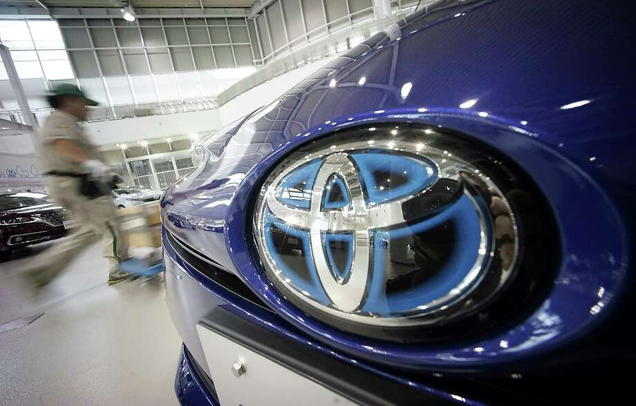 A worker walks past a car at a Toyota showroom in Tokyo on Wednesday as the company announces another recall. Photo: Eugene Hoshiko, STF / Copyright 2016 The Associated Press. All rights reserved. This material may not be published, broadcast, rewritten or redistribu