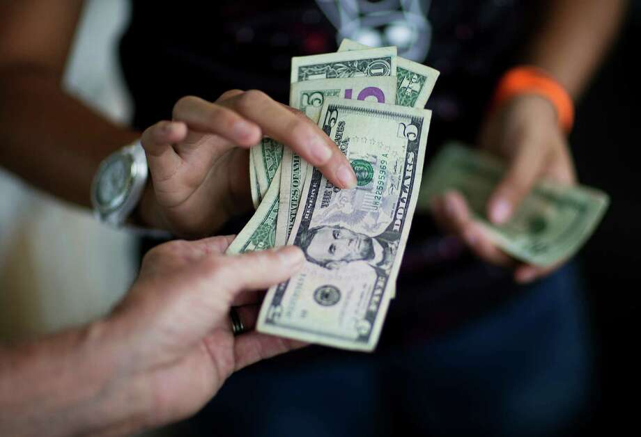 A customer pays for goods while shopping at the Atlanta Farmers Market. Consumer spending grew in May. Photo: David Goldman, STF / Copyright 2016 The Associated Press. All rights reserved. This material may not be published, broadcast, rewritten or redistribu