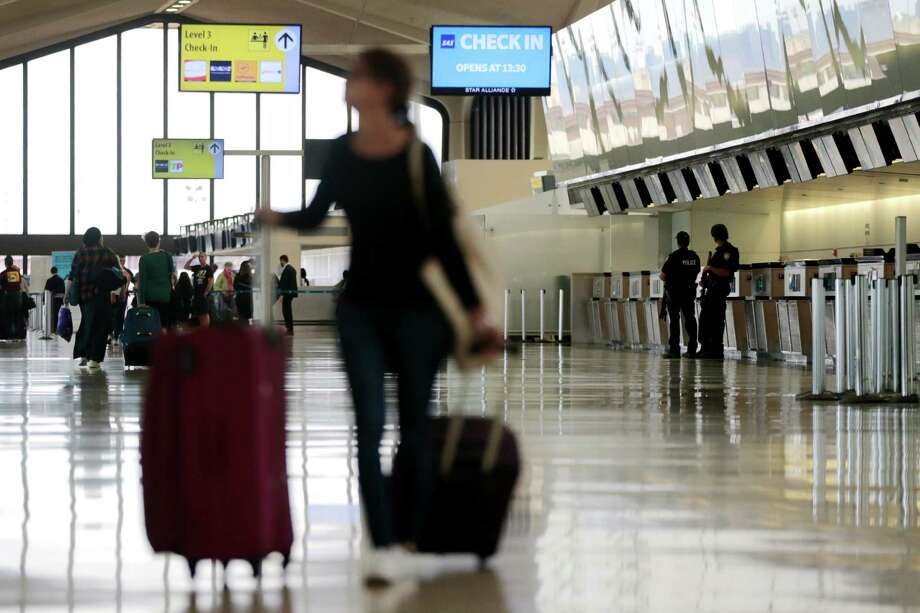 A traveler looks at an information board as officials stand guard at Newark Liberty International Airport last month in Newark, N.J. Photo: Julio Cortez, STF / Copyright 2016 The Associated Press. All rights reserved. This material may not be published, broadcast, rewritten or redistribu