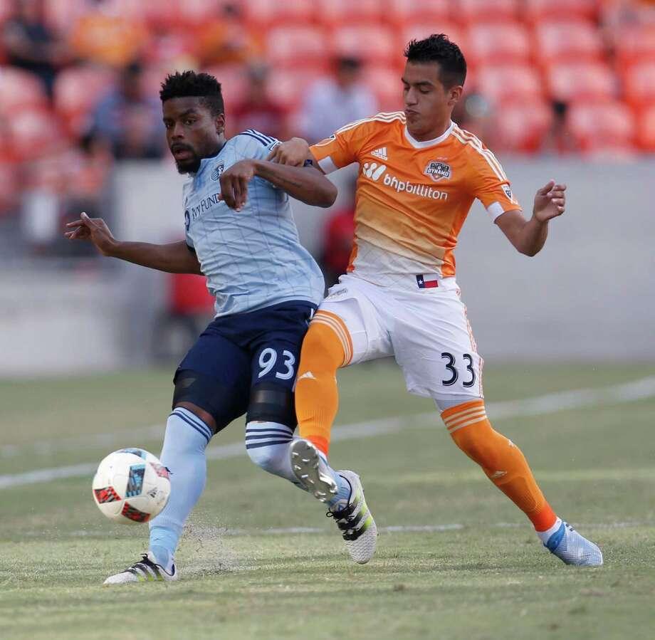 Sporting Kansas City's Soni Mustivar, left, gets the inside track against the Dynamo's Leonel Miranda during Wednesday night's match. Photo: Karen Warren, Staff / © 2016 Houston Chronicle