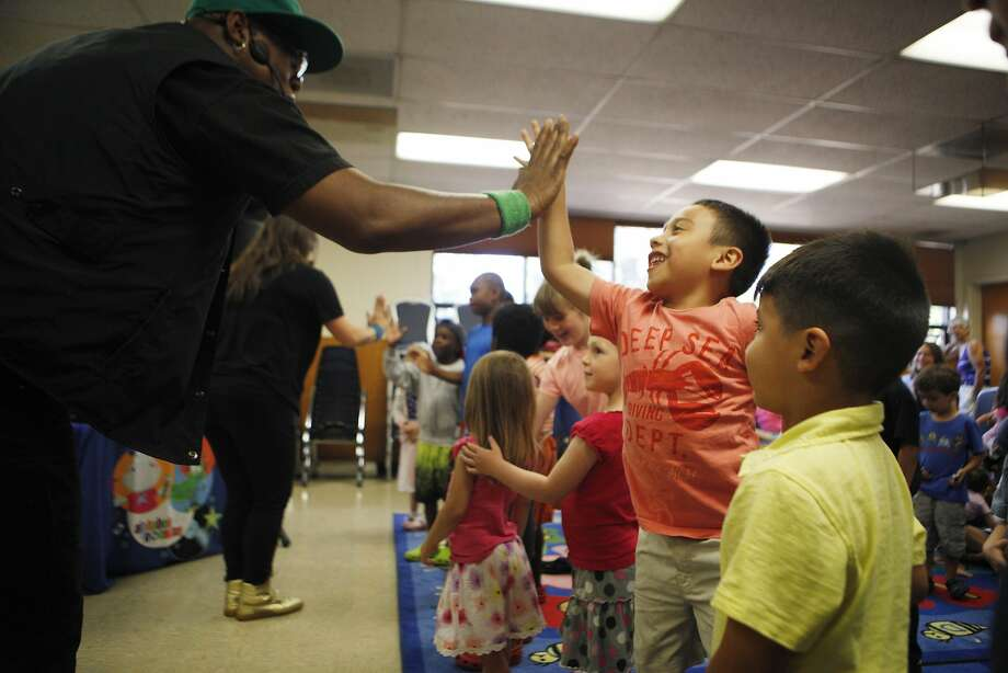 Tommy Shepard of San Francisco of the Alphabet Rockers a high fives a child in the audience on Tuesday, June 28, 2016 at the Oakland Public Library in Oakland, California. They use their songs to teach kids about music and hip hop, as well as nutrition, bullying, race and friendship. Photo: Michael Noble Jr., The Chronicle