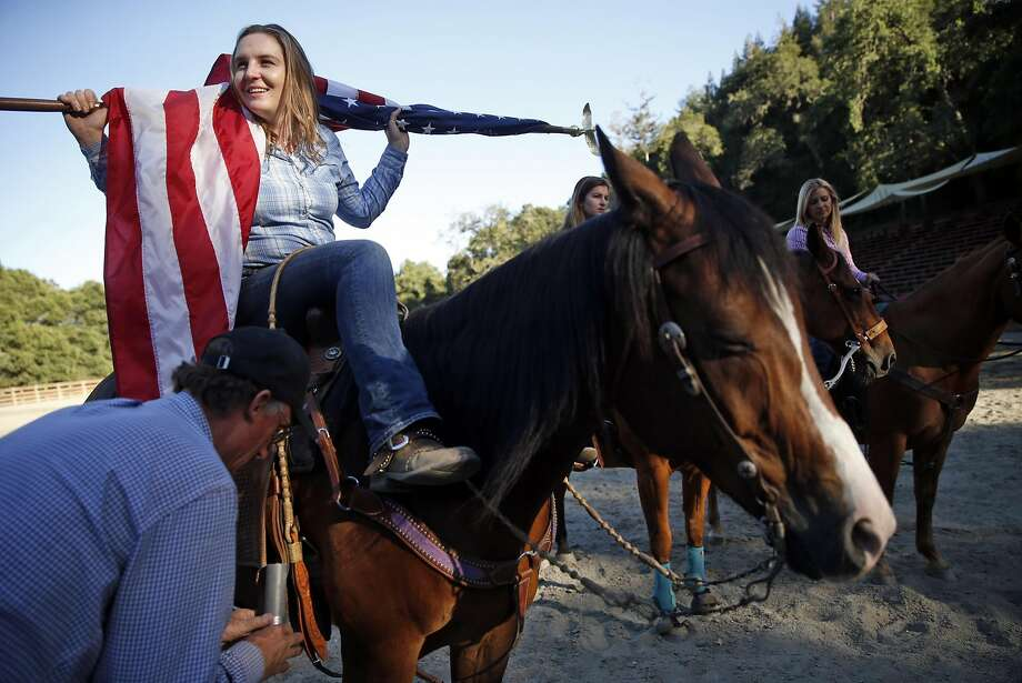 Merilee Raynor, 17, holds the flag as her father, Mike, attaches a flagpole holder before rehearsal of the grand entry for the Woodside Junior Rodeo. Photo: Scott Strazzante, The Chronicle