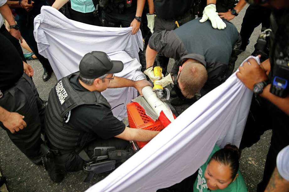 Philadelphia Police officers use a circular saw in an attempt to separate protesters joining their arms together with PVC pipes in Philadelphia on Tuesday, June 28, 2016. Authorities said five people were arrested after the immigration protest that blocked an interstate off-ramp in Philadelphia. Photo: Michael Bryant, AP / Associated Press