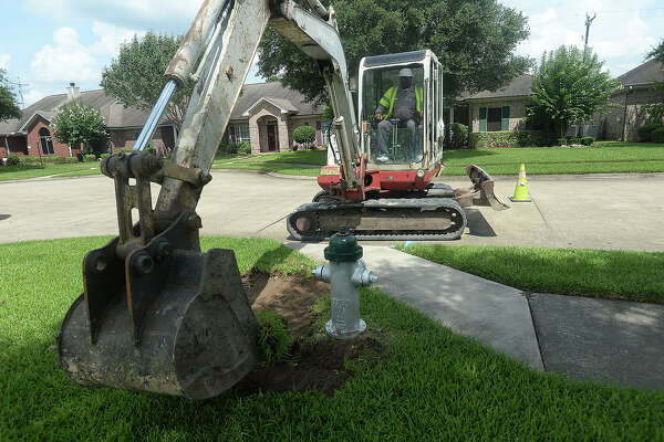 Workers with the City of Beaumont's water department dig around a fire hydrant in a neighborhood off of Delaware and Major as they prepare for Thursday's overnight water shut off and repair work. This will be the second water shut off in the area since work began on sewer and water lines last week. Many residents have expressed concern over the city's efforts to adequately warn and prepare residents. Photo taken Tuesday, June 28, 2016 Kim Brent/The Enterprise