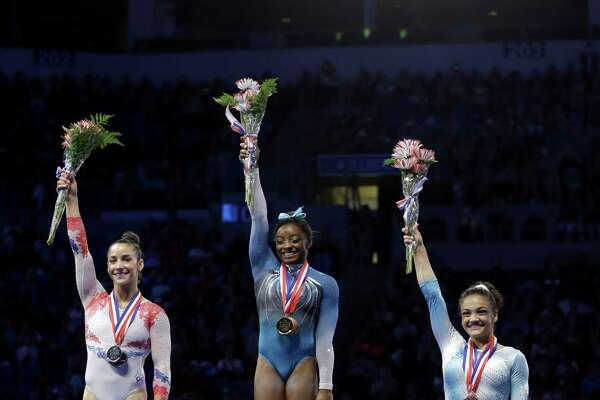 First place finisher Simone Biles, center stands on the podium with second place finisher Aly Raisman and third place finisher Lauren Hernandez during the U.S. women's gymnastics championships Sunday, June 26, 2016, in St. Louis. (AP Photo/Jeff Roberson)