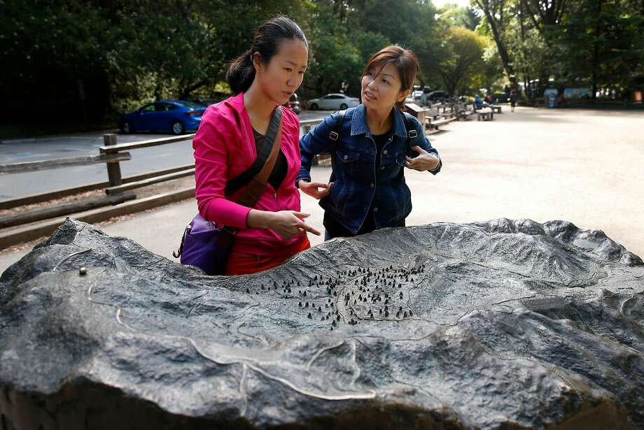 Lisdiana Cendana (left) and Rebecca Felix study a relief model at the entrance to Muir Woods National Monument, where the Park Service is considering a plan to remove a parking lot. Photo: Paul Chinn, The Chronicle