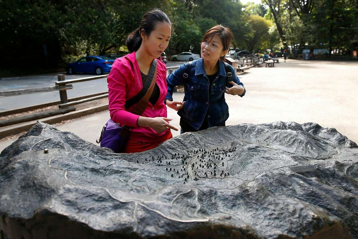 Lisdiana Cendana (left) and Rebecca Felix study a relief model of the area at the entrance to Muir Woods National Monument in Mill Valley, Calif. on Wednesday, June 29, 2016. The National Park Service is considering a plan to remove a parking lot and reduce a wide pedestrian area at the entrance to the park and restore the natural habitat along nearby Redwood Creek.