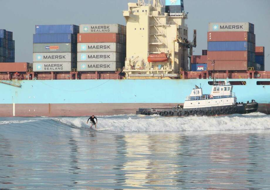 A surfer takes advantage of the wake of a passing cargo ship. James Fulbright built his business around tanker surfing. / Tanker Surf Charters