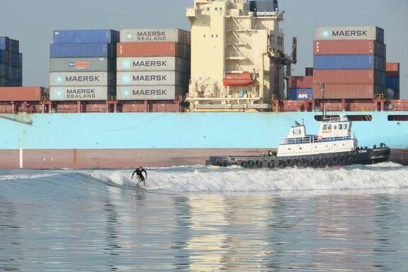 A surfer takes advantage of the wake of a passing cargo ship. James Fulbright built his business around tanker surfing.
