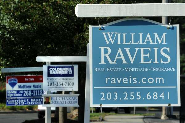 Multiple real estate signs line up along North Ave. in Bridgeport, Conn.