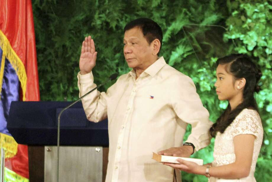 New Philippine President Rodrigo Duterte is sworn in as president. His daughter, Veronica, holds the Bible during the inauguration ceremony at Malacanang Palace in Manila. Photo: Associated Press