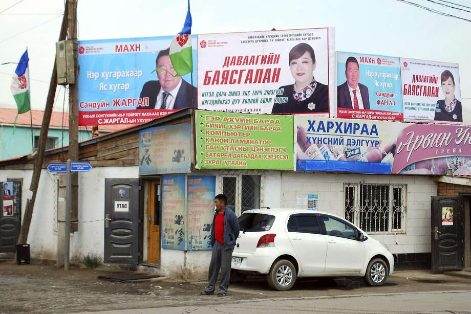 In this Thursday, June 16, 2016 photo, a man stands near a building with billboards for candidates from the Mongolian People's Party (MPP), left, and Democratic Party (DP), right, in the Songinokhairkhand district of Ulaanbaatar, Mongolia. The head of Mongolia's national election commission said Thursday, June 30, 2016, that the opposition MPP won 65 out of 76 seats in the national legislature, a decisive victory in parliamentary elections in the landlocked nation where a fall in commodity prices has sent the economy into a sharp decline. (AP Photo/Ganbat Namjilsangarav) Photo: Ganbat Namjilsangarav, Associated Press