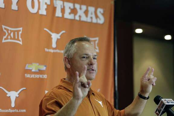 "New Texas baseball head coach David Pierce flashes the ""Hook'em Horns"" sign during a news conference on June 30, 2016, in Austin."