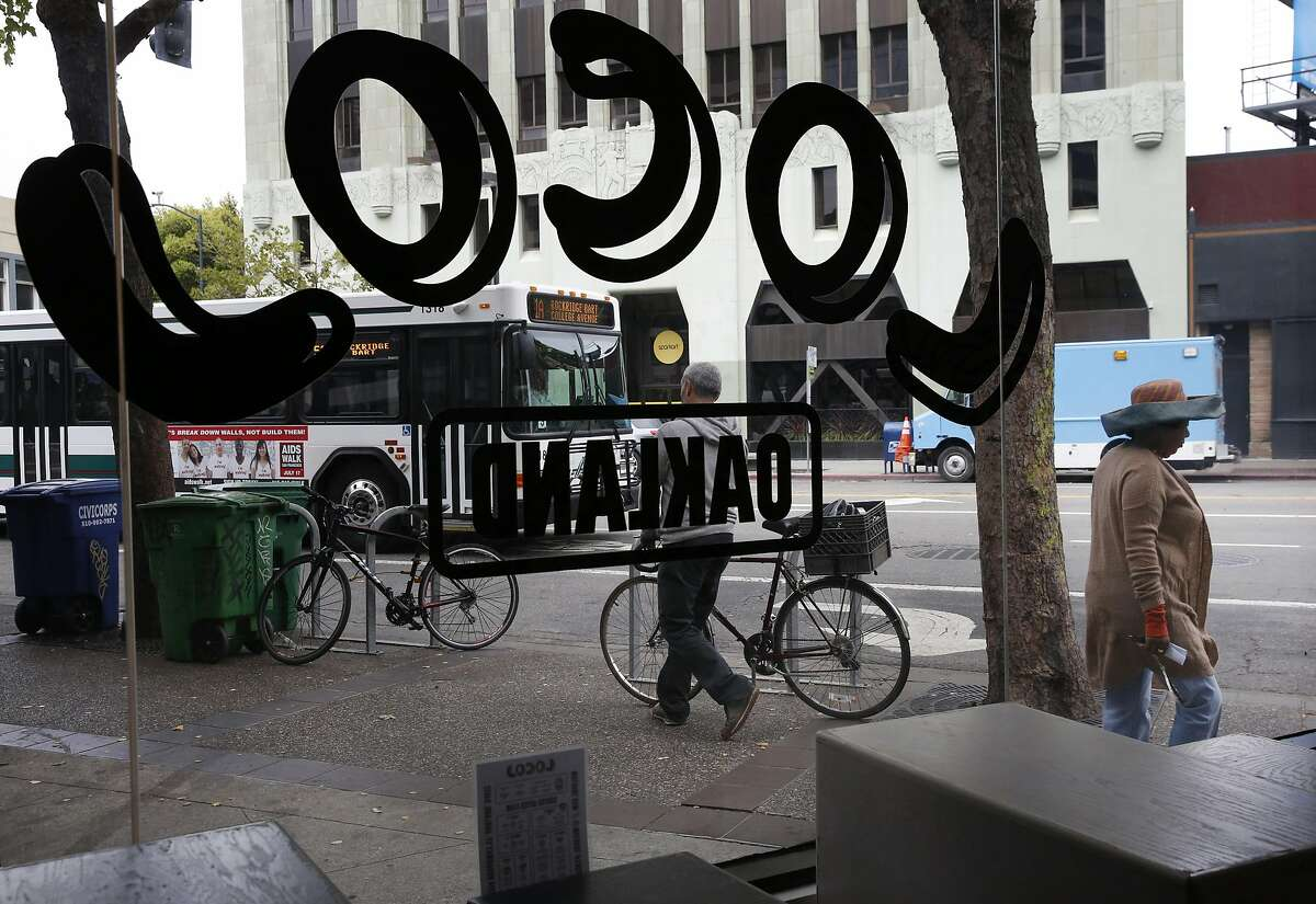 Pedestrians walk past LocoL restaurant June 29, 2016 in Oakland, Calif.