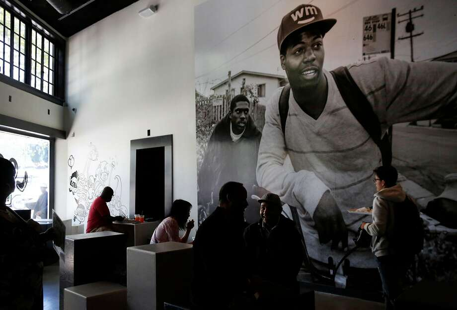 Nidamu Khuthaza, center, and Vincent Leon, right center, wait for their lunch in front of a large print by Travis Jensen in LocoL restaurant June 30, 2016 in Oakland, Calif. Photo: Leah Millis / The Chronicle